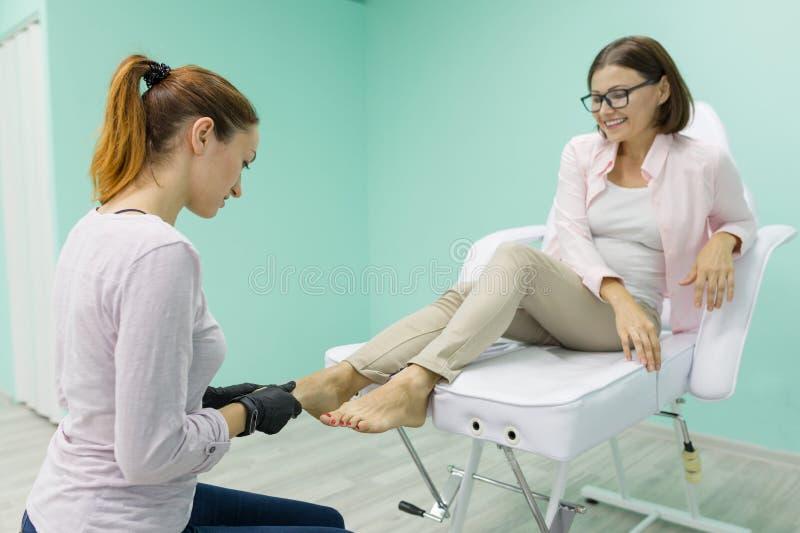 Het proces van de close-uppedicure Jonge vrouw die professionele pedicure, schoonheidssalon, nagelverzorging krijgen stock afbeelding