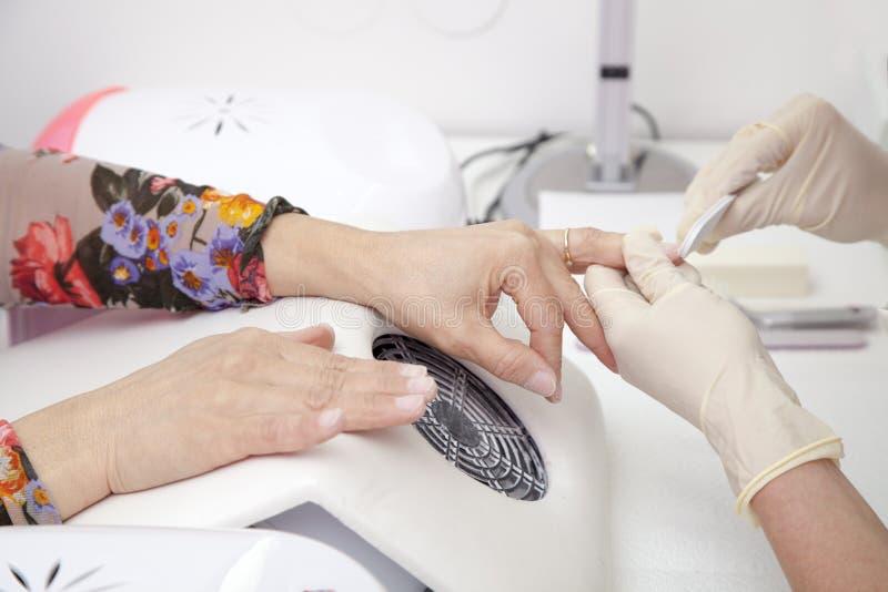Het proces van de manicure bij de vrouwelijke hand Franse manicure, die spijkeruitbreiding maakt royalty-vrije stock afbeeldingen