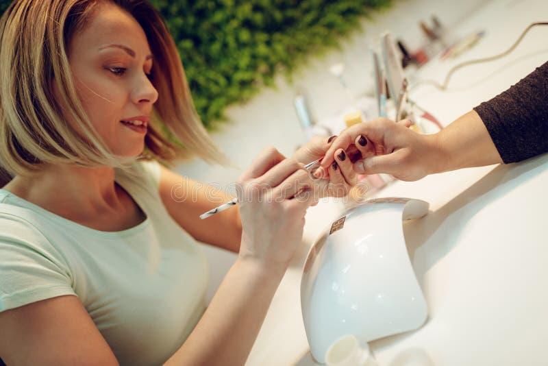 Het proces van de manicure? De vrouwelijke handen? stock foto