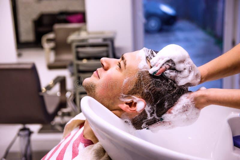 Het professionele haar van de kapperwas aan haar knappe cliënt royalty-vrije stock foto