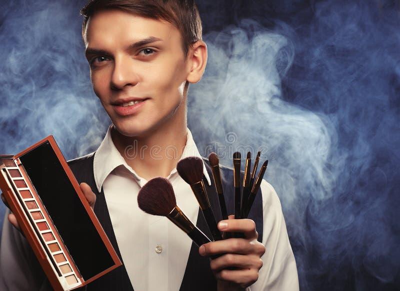 Het professionele make-upkunstenaar stellen in studio, houdt een palet stock afbeelding