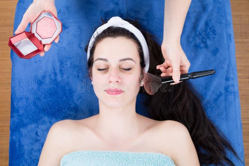 Het professionele make-upkunstenaar van toepassing zijn bloost aan mooie schoonheids donkerbruine jongelui stock fotografie