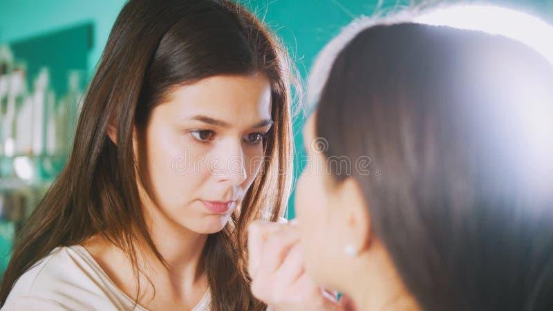 Het professionele stilist vrouwelijke doen maakt jonge vrouw voor spiegel in schoonheidssalon goed royalty-vrije stock foto
