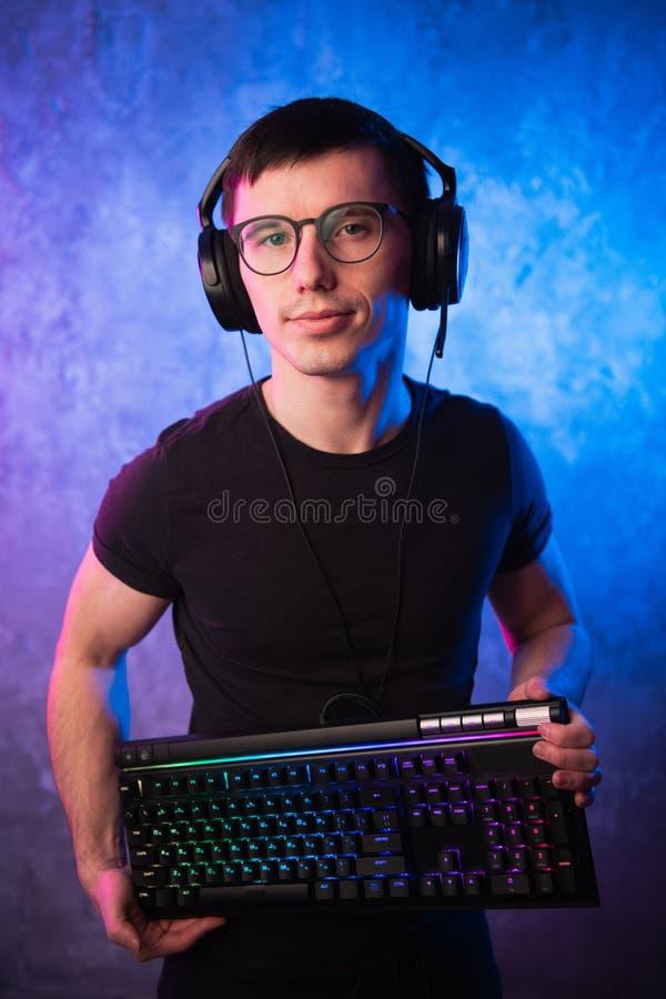 Het professionele toetsenbord van het de holdingsgokken van Jongensgamer over kleurrijk roze en blauw neon stak muur aan Het conc stock afbeelding
