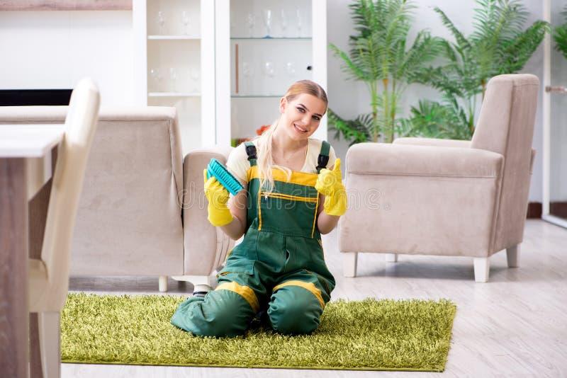 Het professionele vrouwelijke schonere schoonmakende tapijt stock foto