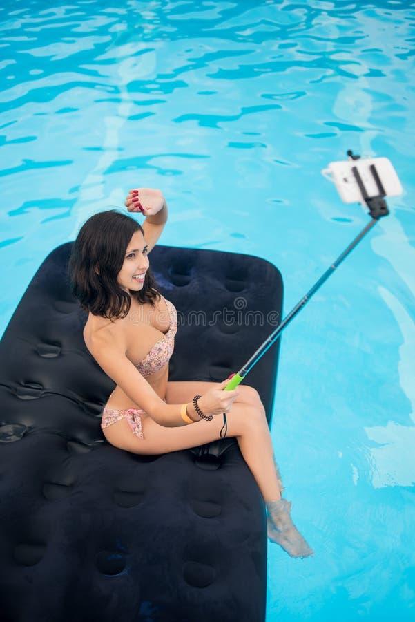 Het profiel van een jong brunette maakt selfie foto op de telefoon met selfiestok op matras in pool Mening van hierboven royalty-vrije stock afbeeldingen