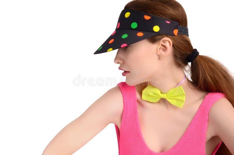 Het profiel van een jonge vrouw die een kleurrijke polka dragen stippelde hoed en een neon groene bowtie. stock foto's