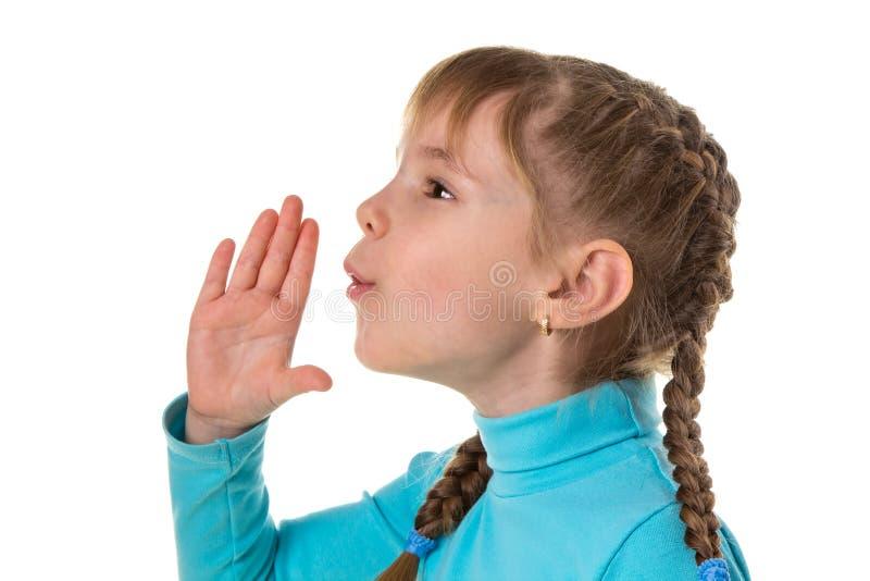 Het profiel van een klein meisje blaast met een lege die hand, op witte landschapsachtergrond wordt geïsoleerd stock foto