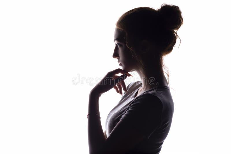 Het profiel van een mooi meisje met kinhand die contemptuously kijken naar, zekere jonge vrouw op een wit isoleerde achtergrond royalty-vrije stock afbeelding