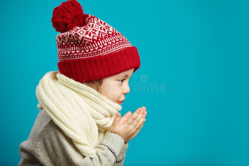 Het profielportret van meisje in rode Kerstmishoed, vouwde samen haar handen en zijdelings blazend, geïsoleerd schot stock afbeeldingen