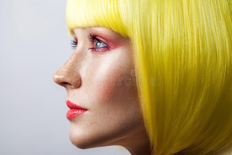 Het profielportret van het schoonheids zijaanzicht van leuk jong kalm vrouwelijk model met sproeten, rode make-up en gele pruik,  royalty-vrije stock foto