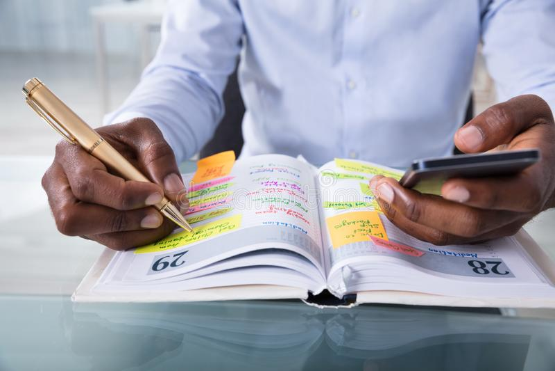 Het Programma van zakenmanholding cellphone writing in Agenda met Pen royalty-vrije stock foto's