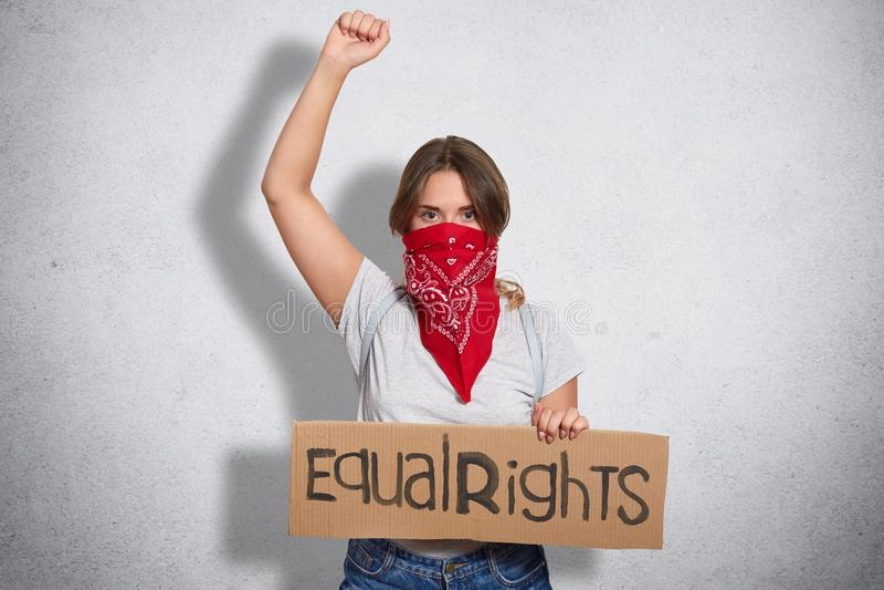 Het protestconcept van vrouwen Het ernstige jonge Europese wijfje met bandana op gezicht, houdt plaat met inschrijving, opheft bi royalty-vrije stock afbeelding