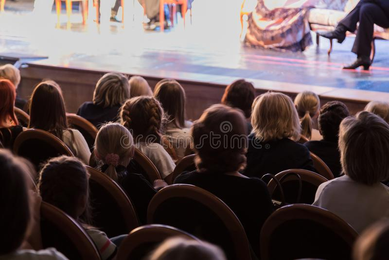 Het publiek in het theater die op een spel letten Het publiek in de zaal: volwassenen en kinderen stock afbeeldingen