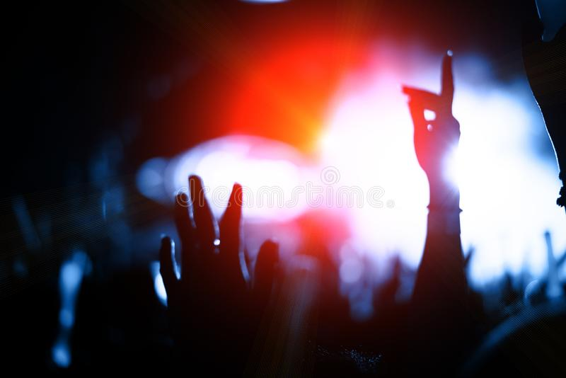 Het publiek van de silhouetmenigte in overleg met handen heft bij muziek F op stock afbeeldingen