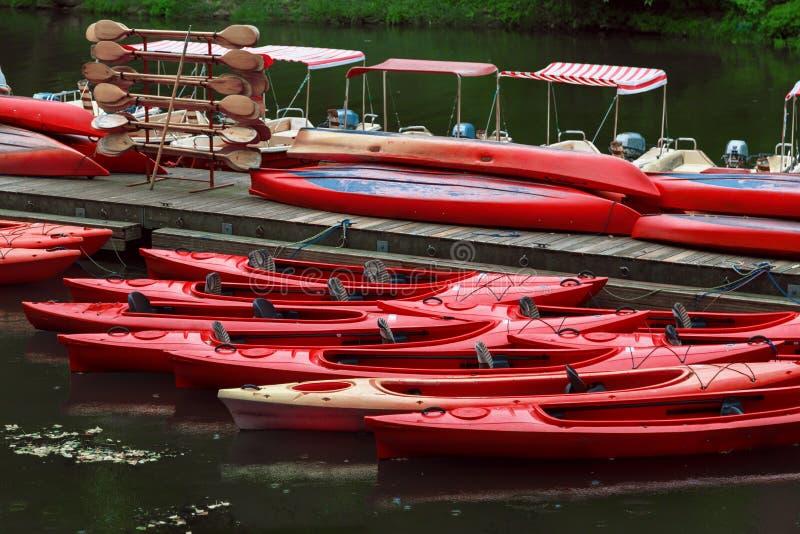 Het punt van de kajakshuur De rode boten op pijler stock afbeeldingen