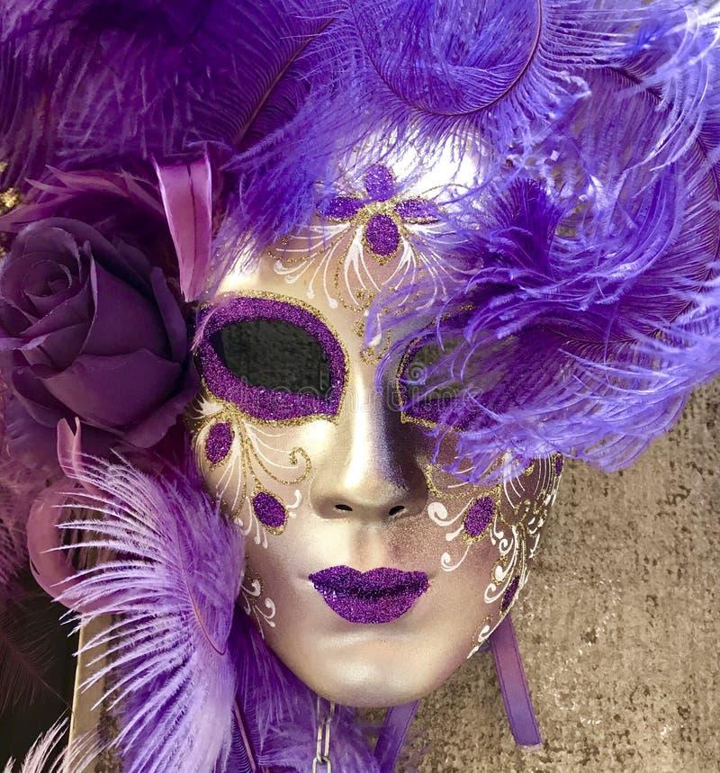 Het purpere en gouden Venetiaanse maskerademasker hangen op een muur stock fotografie