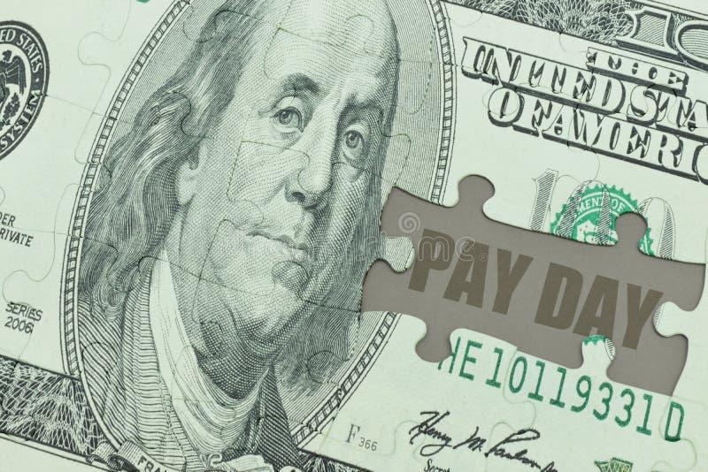 Het raadsel met het dollarbankbiljet en de tekst betalen dag royalty-vrije stock afbeelding