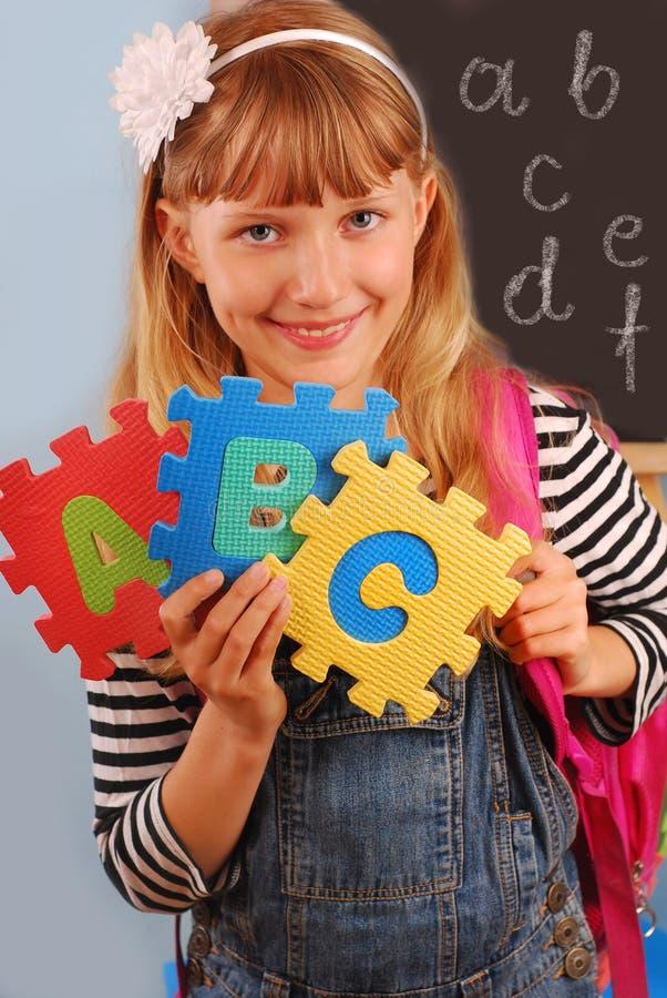 Het raadsel van de holdingsbrieven van het schoolmeisje stock afbeeldingen