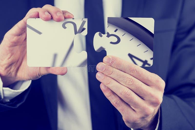 Het raadselstukken van de zakenmanholding van een klok stock foto