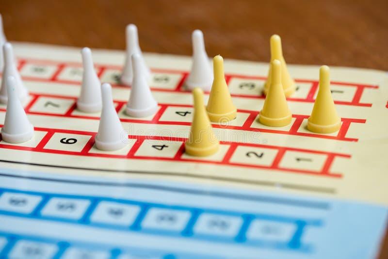het raadsspel met kleurenpanden, gele spaanderleider, witte concurrenten royalty-vrije stock fotografie