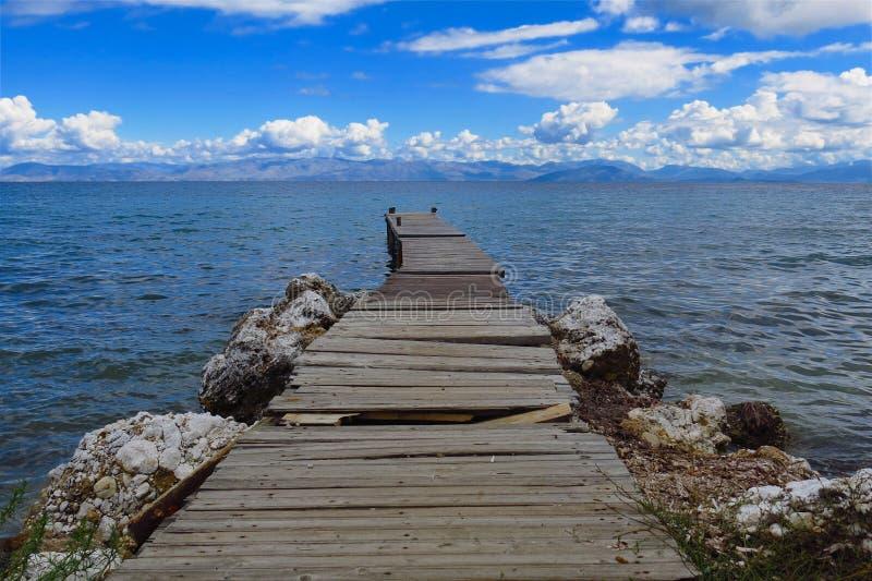 Het rachitische dok breidt zich in blauwe overzees onder blauwe hemel uit stock foto's