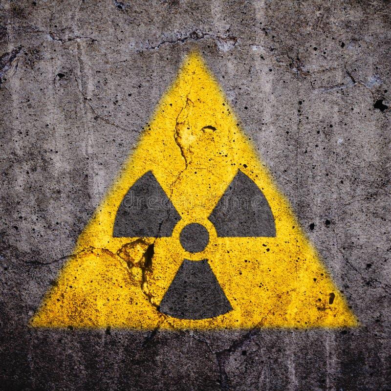Het radioactieve atoom de waarschuwingssymbool van het ioniserende stralinggevaar in driehoekige gele vorm schilderde massieve ge stock foto