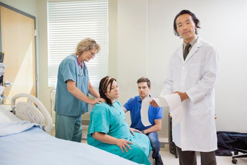 Het Rapport van artsenexplaining fetal heartbeat aan stock foto's
