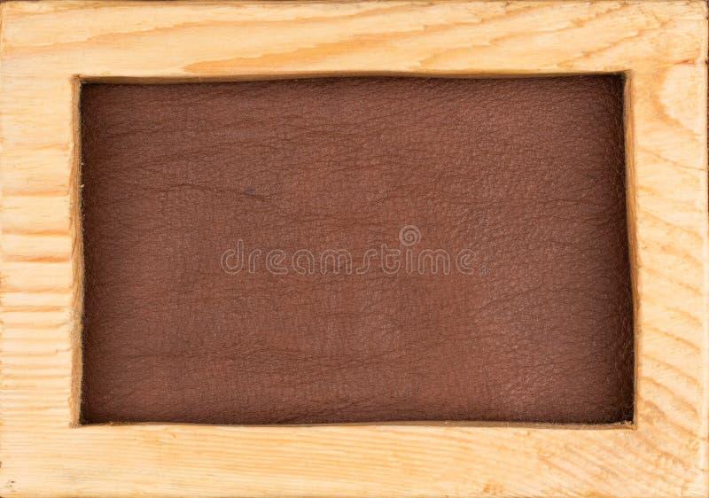 Het rechthoekige die kader van licht hout wordt gemaakt ligt op bruin natuurlijk leer Textuur van een boom royalty-vrije stock afbeeldingen