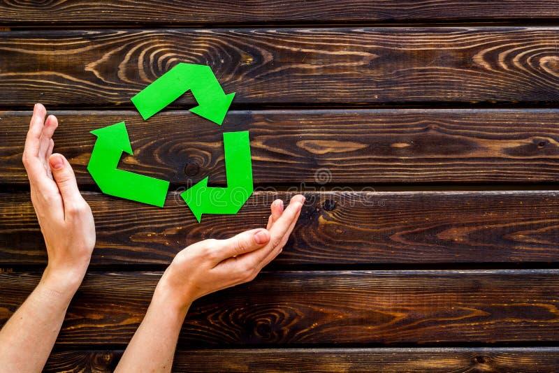 Het recycling van symbool in handen voor ecologie op houten hoogste mening als achtergrond copyspace stock fotografie