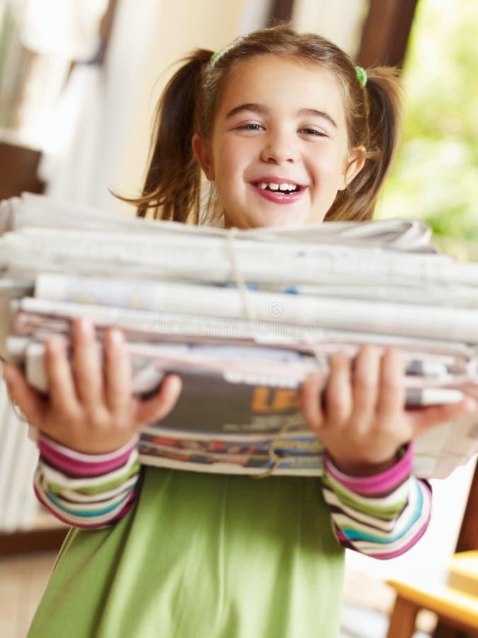 Het recyclingskranten van het meisje stock foto