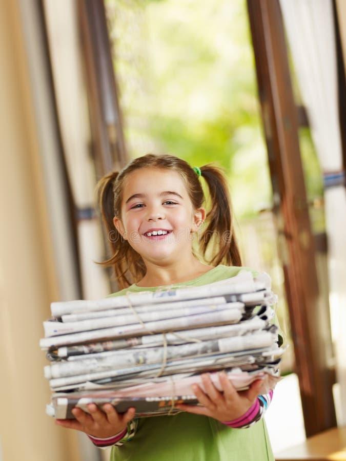 Het recyclingskranten van het meisje royalty-vrije stock foto
