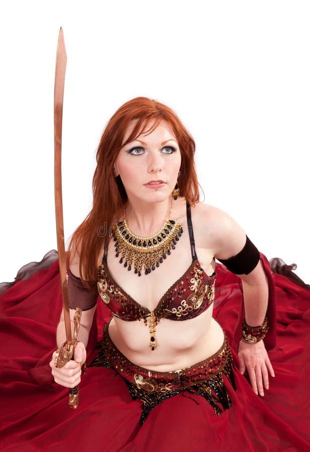 Het Red-headed buikdanser stellen met zwaard royalty-vrije stock fotografie