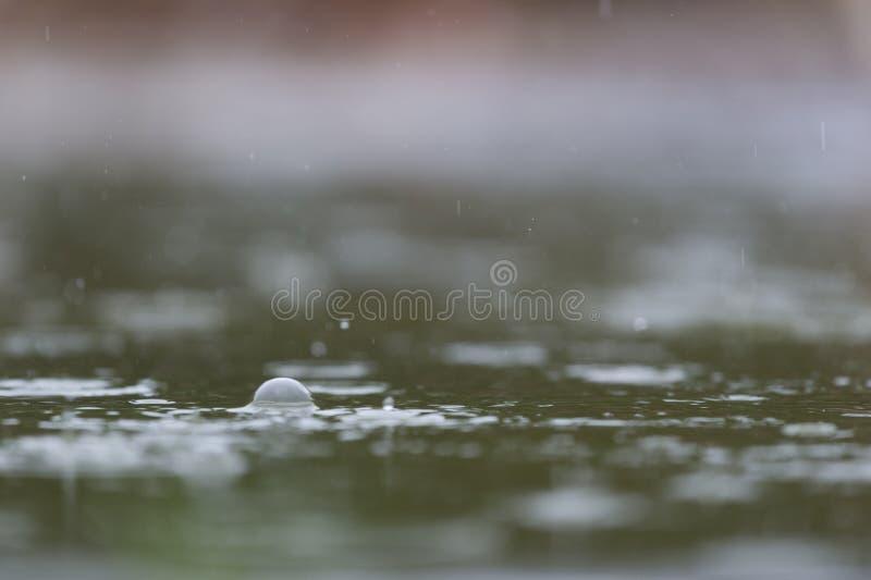 Het regenen in water stock foto