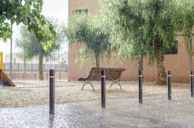 Het regent in een kinderen` s speelplaats, regendalingen het vallen stock fotografie