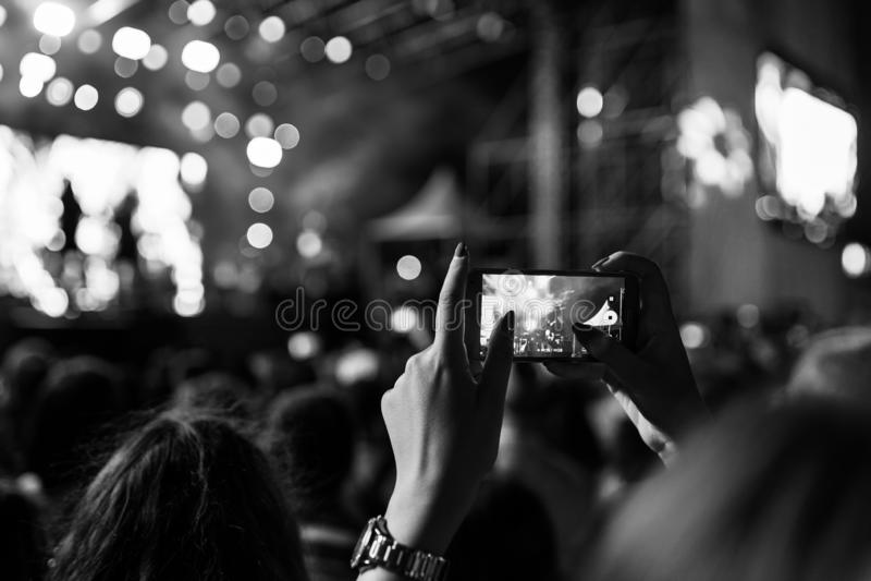 Het registreren van een overleg op een mobiele telefoon van de menigte, zwart-witte versie stock fotografie