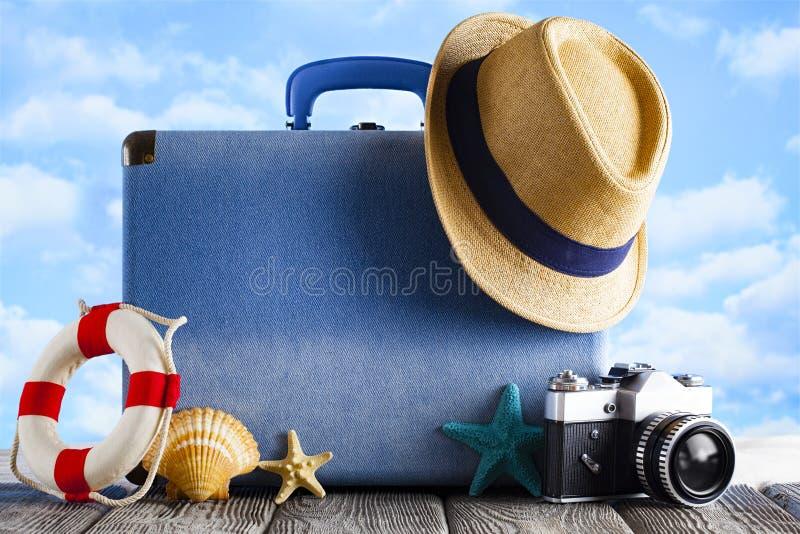 Het reisconcept voor de zomervakantie - koffer, hoed en fotocamera op strandachtergrond stock afbeeldingen