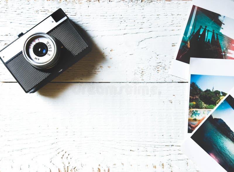 Het reismodel met foto's en vlakte van de camera de hoogste mening legt op houten witte achtergrond stock afbeelding