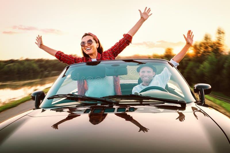Het reizen door auto - het gelukkige paar in liefde gaat door cabriolet auto in s