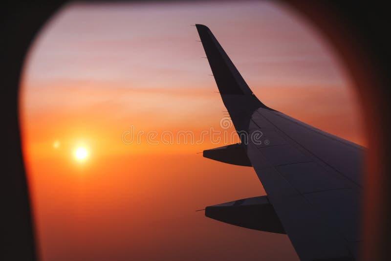 Het reizen door vliegtuig Mening van het venster aan de wolken en de dageraad stock afbeeldingen