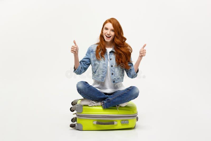 Het reizen en Levensstijlconcept De jonge opgewekte Kaukasische vrouwenzitting op de bagage valise het tonen van duim Geïsoleerde stock afbeelding