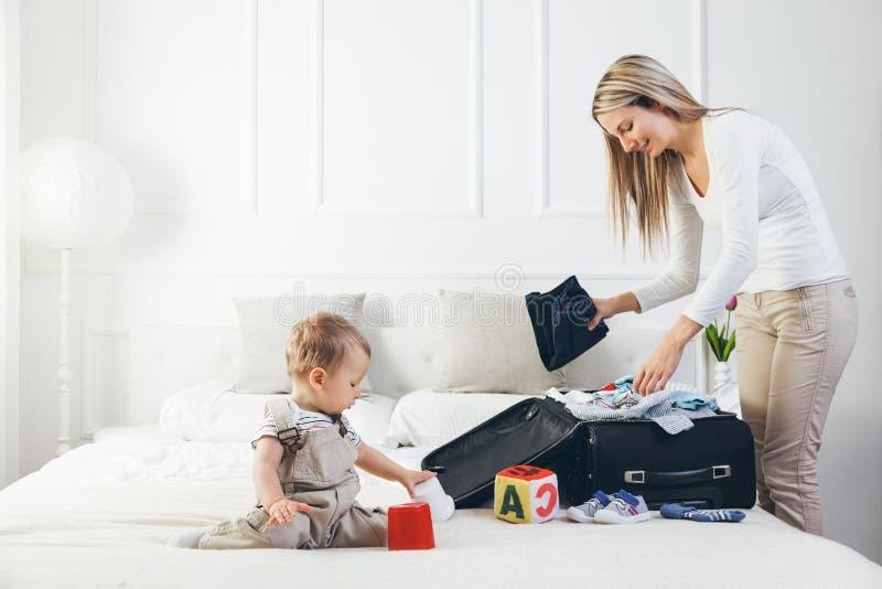 Het reizen met jonge geitjes Gelukkige moeder met haar kleren van de kindverpakking voor vakantie royalty-vrije stock afbeelding
