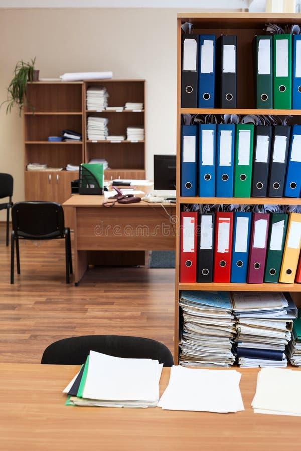 Het rek met kleurendocument omslagen is in een lege bureauruimte, niemand stock foto's
