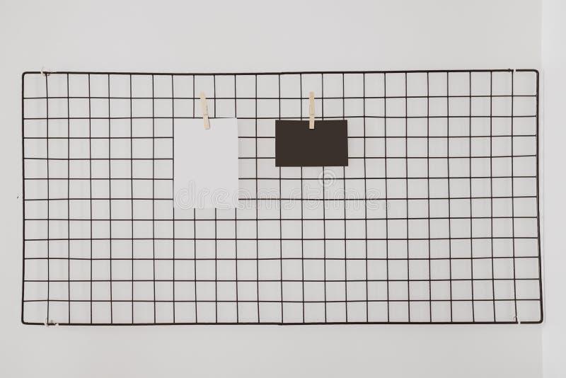 Het rek van de prentbriefkaarhanger op witte muurachtergrond stock fotografie