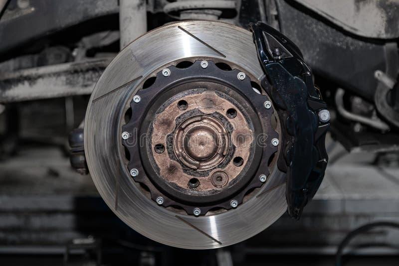 Het remsysteem van de auto met het wiel dat met de schijf, de stootkussens, de hub en de koelgaten tijdens onderhoud en vervangin stock afbeelding