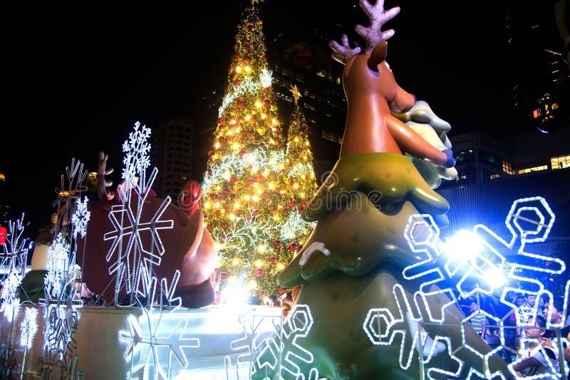 Het rendierstandbeeld en het licht van kleurrijk verfraaien mooi op Kerstboomviering stock afbeelding
