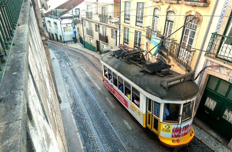Het Retro tramauto drijven voorbij huizen op kleine smalle straat, zoals een toeristische attractie royalty-vrije stock fotografie