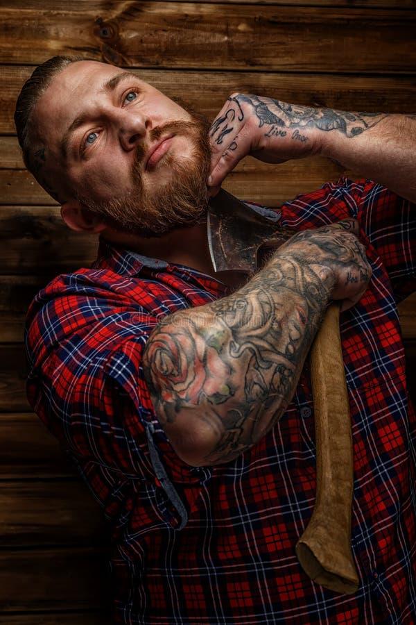 Het reusachtige brutale mannetje met tatoegeringen scheert zijn baard stock fotografie
