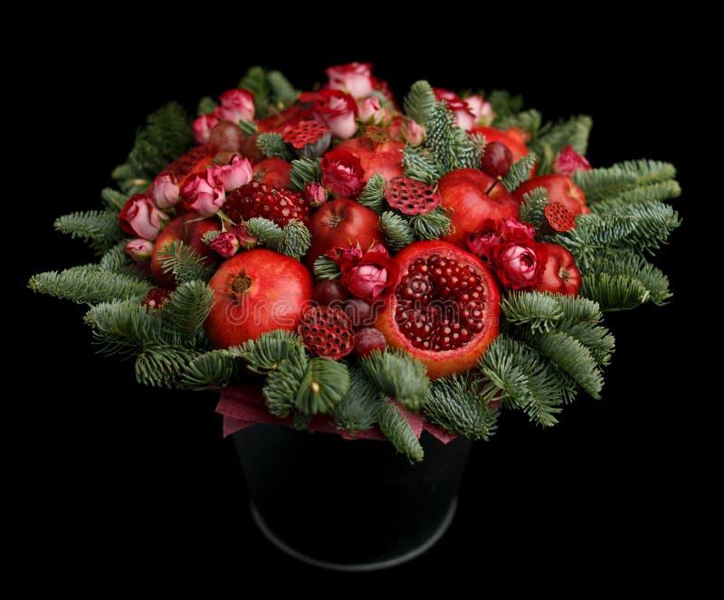 Het reusachtige eetbaar fruitboeket die uit granaatappels, appelen, druiven bestaan, nam bloemen en spartakjes op zwarte achtergr stock afbeelding