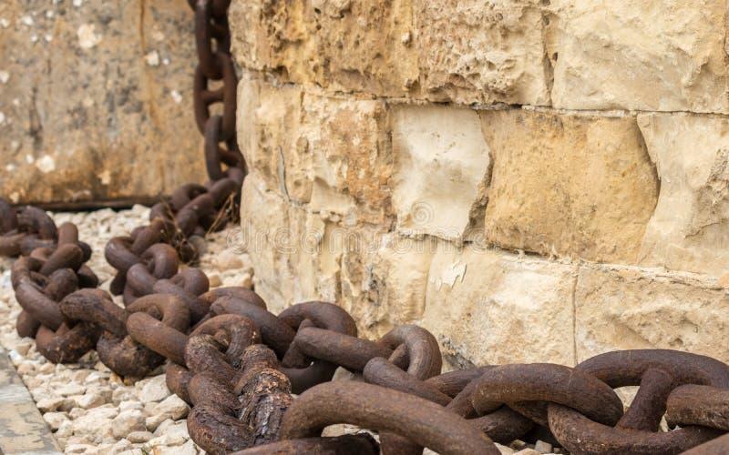 Het reusachtige, oude en roestige ketting hangen neer van zandsteenmuur in Fort St Elmo, Valletta, Malta royalty-vrije stock foto